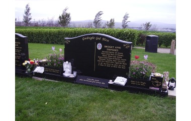 Double- width grave (4ft wide memorial), ogee with chamfered edges, splayed base, planters and vases, black granite, gilded inscription and design